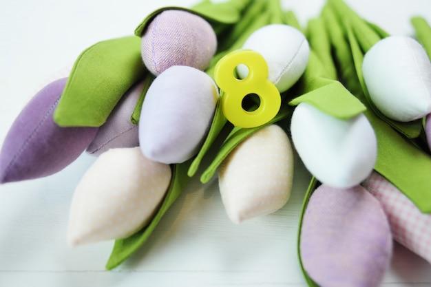 Biglietto di auguri per l'8 marzo donne. un mazzo di tulipani su una superficie di legno con la figura 8.