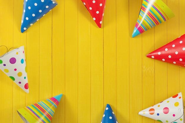 Biglietto di auguri per la festa di carnevale. cappello e candele di partito su fondo di legno.