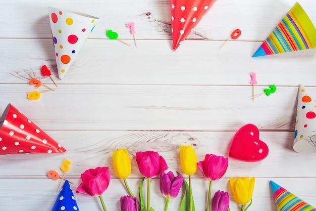 Biglietto di auguri per la ragazza principessa. tulipani, cappello da festa, candela, cuore rosso su legno
