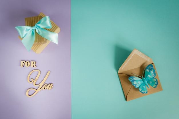 Biglietto di auguri per te su uno sfondo viola - menta con scatole regalo, busta e farfalla