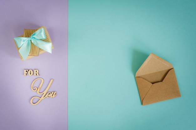 Biglietto di auguri per te su uno sfondo viola - menta con scatole regalo e busta.