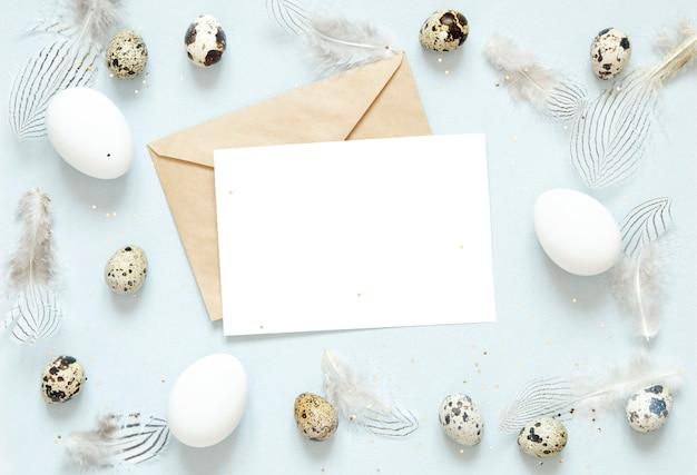 Biglietto di auguri vuoto, busta kraft. composizione di pasqua con le uova di pasqua e piume su sfondo blu.