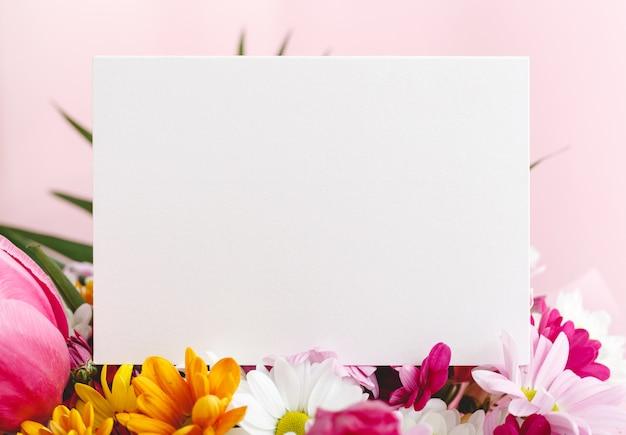 Biglietto di congratulazioni in bouquet di fiori su sfondo rosa.