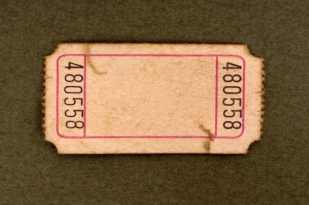 Biglietto di ingresso in bianco tinto e danneggiato su uno sfondo di carta marrone chiazzato.