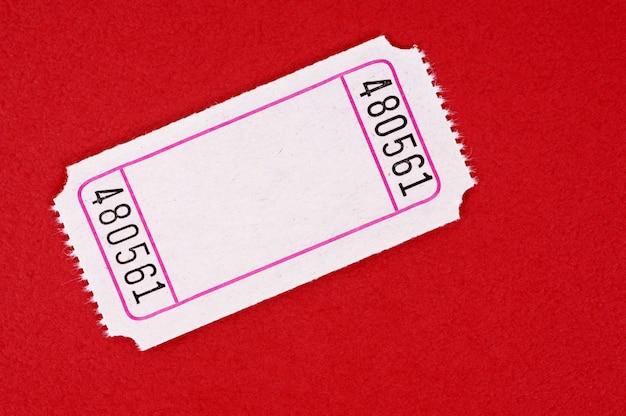 Biglietto di ingresso vuoto su uno sfondo di carta rossa chiazzato