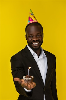 Bigné allegro di compleanno della tenuta dell'uomo di colore