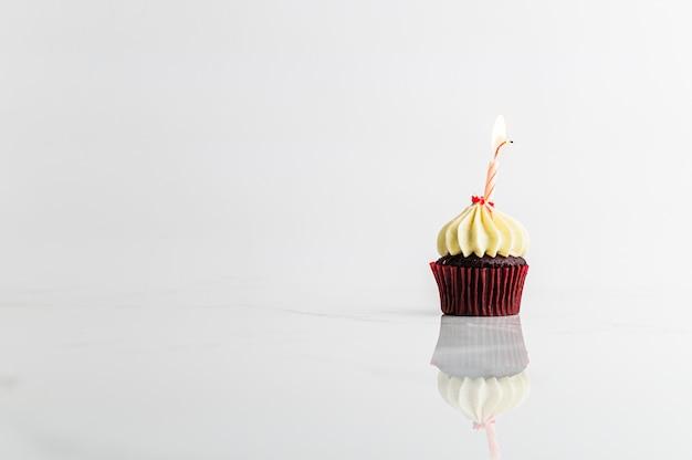 Bigné con la festa di compleanno della candela su fondo bianco, concetto di anniversario