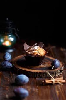 Bigné del muffin ai mirtilli su un fondo di legno scuro con le prugne.