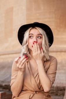 Bigné della tenuta della donna e posare mentre coprendo bocca di mano