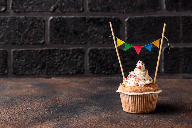 Bigné di compleanno con crema e ghirlanda colorata