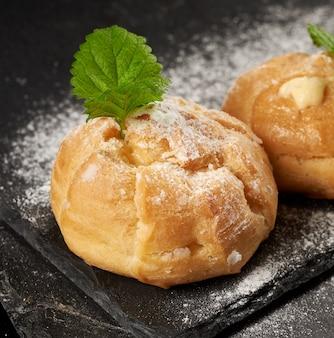 Bignè di crema pasticcera al forno e cosparsi di zucchero a velo e decorati con una foglia di menta