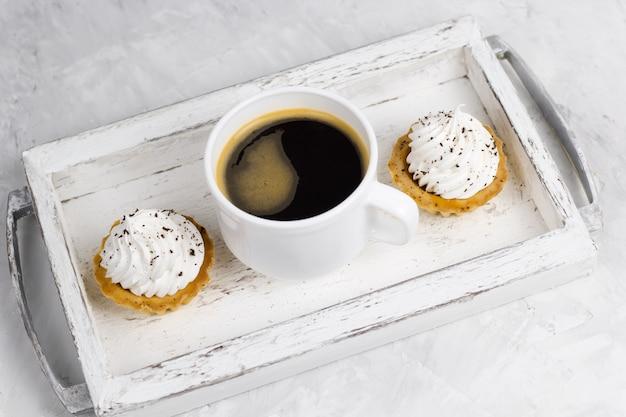 Bigné di vista superiore con crema decorata con di pepita di cioccolato e tazza di caffè su un fondo concreto del vassoio di legno d'annata