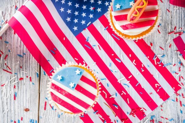 Bigné patriottici di usa sopra le bandiere sulla tavola di legno