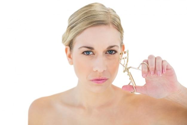 Bigodino di ciglia della holding della giovane donna bionda aggrottante le sopracciglia