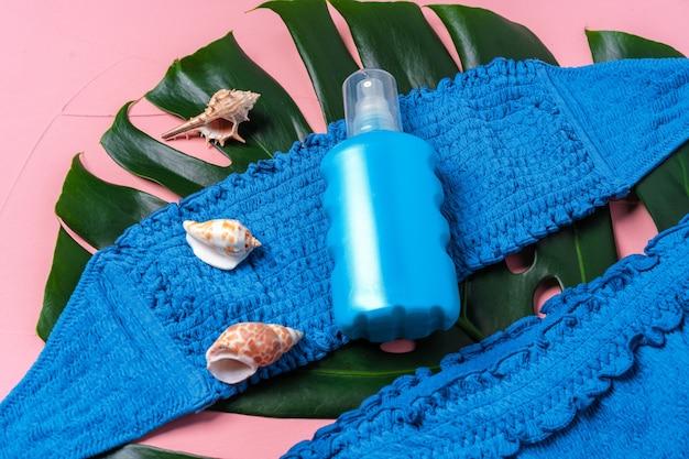 Bikini blu con flacone spray per la protezione solare e foglia di monstera e conchiglie