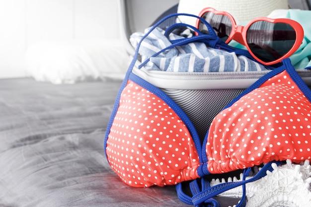 Bikini color corallo vivente e accessori estivi nel bagaglio