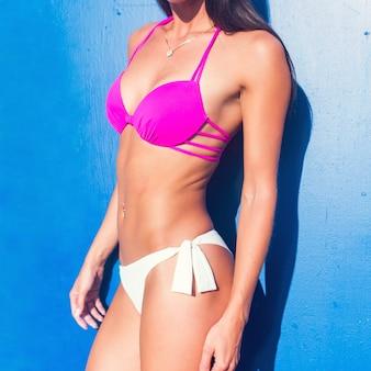 Bikini corpo donna abbronzatura modello irriconoscibile in costume da bagno con pelle abbronzata liscia.