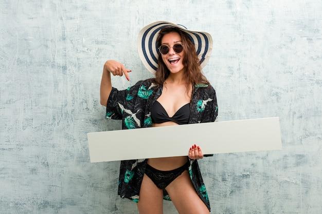 Bikini d'uso della giovane donna europea e tenere un cartello