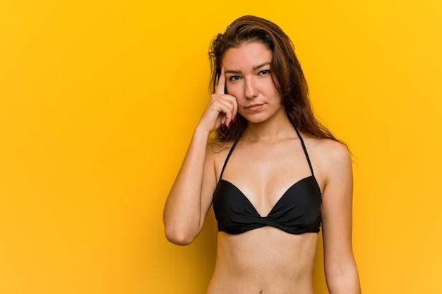 Bikini da portare della giovane donna europea che indica la sua tempia con la barretta, pensante, messa a fuoco su un compito.