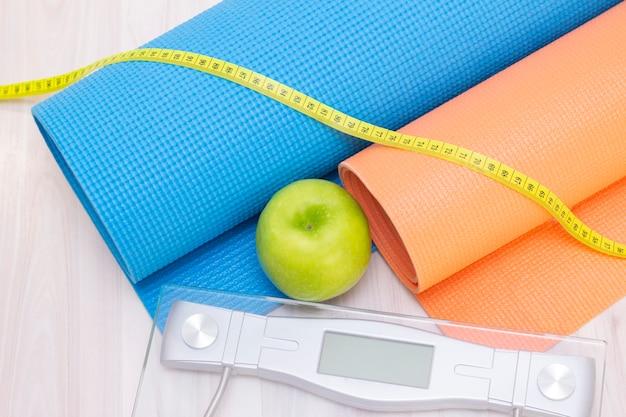 Bilance, mela verde, metro e stuoie sportive su una superficie di legno chiaro. preparazione per la stagione estiva e il concetto di spiaggia, perdita di peso e sport