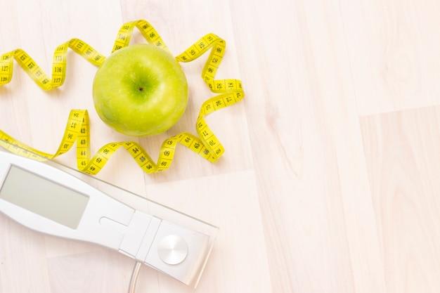 Bilance, mela verde, nastro di misurazione su uno sfondo in legno chiaro. preparazione per la stagione estiva e il concetto di spiaggia, perdita di peso e sport