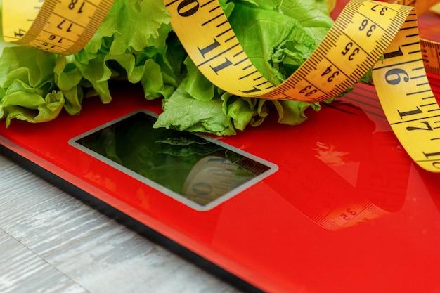 Bilancia elettronica digitale con metro a nastro, lattuga. dieta, concetto dimagrante.