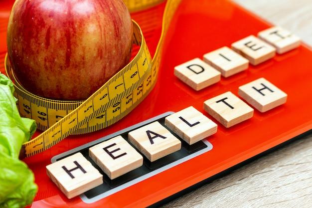 Bilancia elettronica digitale con metro a nastro, lattuga, mela, lettere dieta, concetto dimagrante.