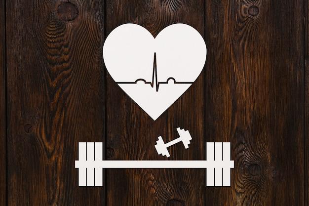 Bilanciere, manubri e cuore con ecocardiogramma. concetto di stile di vita sano