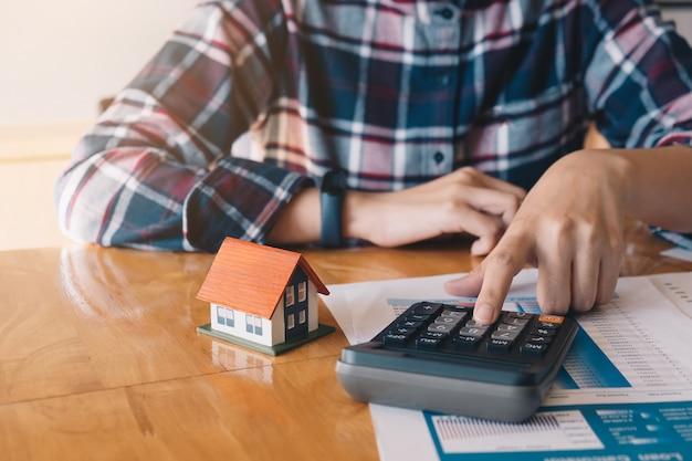 Bilancio calcolatore della donna prima della firma del contratto di progetto del bene immobile con il modello della casa alla tavola nella casa