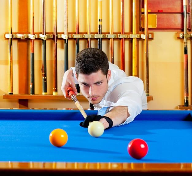 Biliardo vincitore bell'uomo giocando con stecca e palle al club