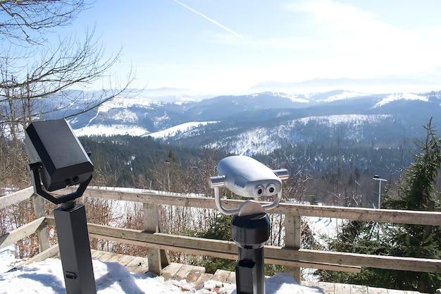 Binocolo sul ponte di osservazione in cima alle montagne innevate; paesaggio invernale.