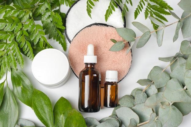 Bio-cosmetici biologici con ingredienti a base di erbe. estratto naturale, olio, siero con foglie fresche. piatto disteso, bellezza fatta a mano e spa, profumo o crema di ingredienti.