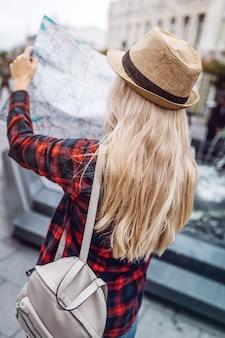 Bionda alla moda con mappa alla ricerca del percorso