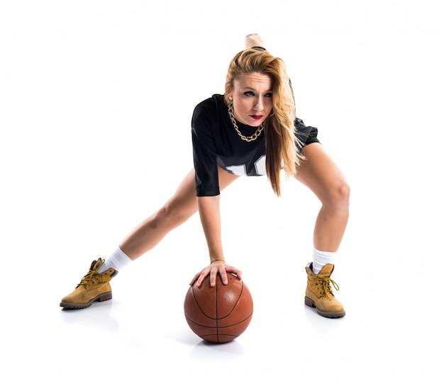 Bionda bella donna che gioca a basket