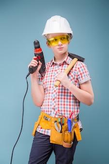 Bionda bionda dell'adolescente nel casco della costruzione con un cacciavite e un martello