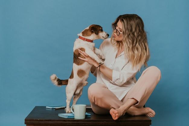 Bionda carina con gli occhiali, vestita con una camicia bianca e pantaloni rosa chiaro, seduta su un tavolo con il suo cucciolo jack russell, che gli dà un bacio. resta a casa durante la quarantena. concetto di covid-19.