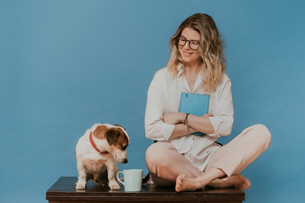 Bionda carina con gli occhiali, vestita con una camicia bianca e pantaloni rosa chiaro, seduta su un tavolo con il suo cucciolo jack russell, lo guarda con tenerezza. resta a casa durante la quarantena. concetto di covid-19.