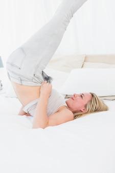 Bionda che lotta per chiudere i suoi jeans