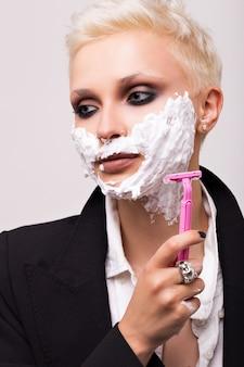 Bionda con un taglio di capelli corto in una giacca nera con schiuma da barba sul viso. rasoio da donna rosa.