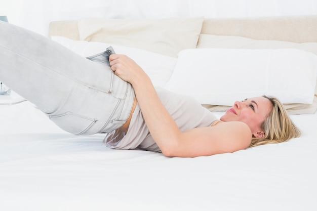Bionda concentrata che costringe a chiudere i suoi jeans