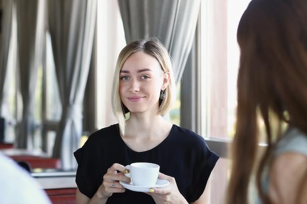 Bionda della donna che parla con amici in un caffè per una tazza di caffè