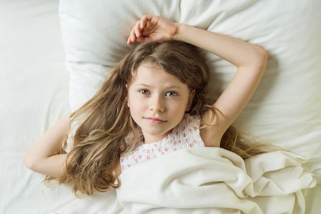 Bionda della ragazza del bambino con capelli ondulati lunghi su un cuscino
