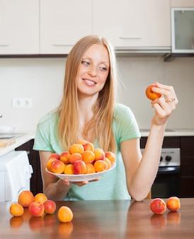 Bionda donna dai capelli lunghi che mangia albicocche nella cucina domestica