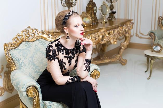 Bionda donna reale su un divano retrò in splendido abito di lusso con un bicchiere di vino in mano. interno. copia spazio