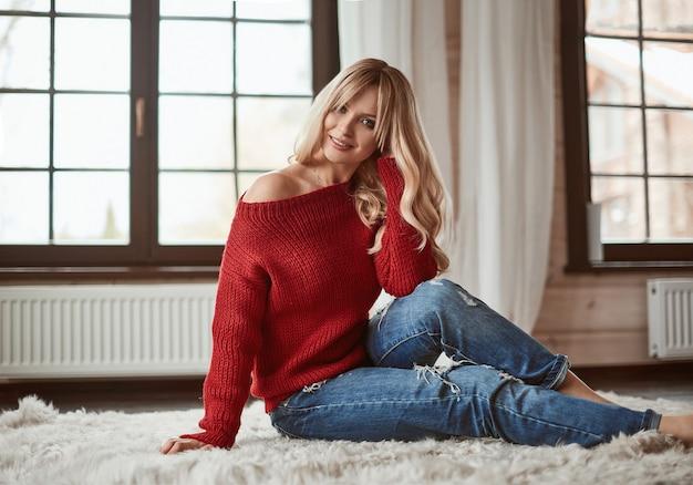 Bionda elegante georgeous che si siede sul tappeto di pelliccia accogliente