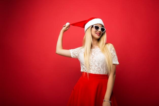 Bionda felice in cappello santa su sfondo rosso isolato. occhiali da sole cerchiati bianchi.