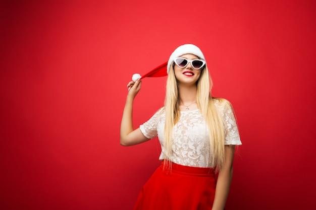 Bionda felice in cappello santa su sfondo rosso isolato