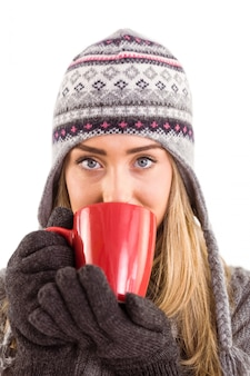Bionda felice in vestiti di inverno che tiene tazza