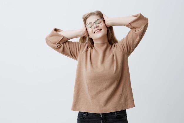 Bionda gioiosa ragazza caucasica che indossa maglione marrone e occhiali da vista, tenendosi per mano sulla testa mentre si diverte al chiuso su sfondo grigio muro di studio, sorridendo ampiamente, dimostrando i denti bianchi e uniformi