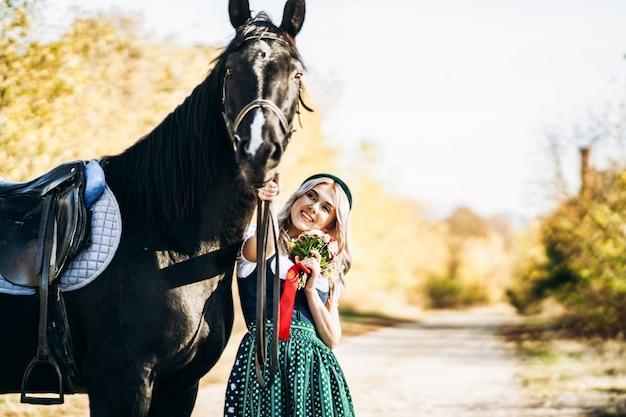 Bionda graziosa in vestito tradizionale che cammina con il grande cavallo nero all'aperto